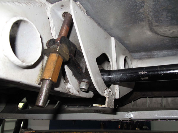 Attachment of driver's side torsion spring to a crossmember under the floorboard.