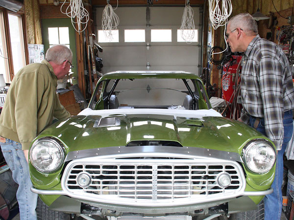 A friend helps with installation of the bonnet assembly.