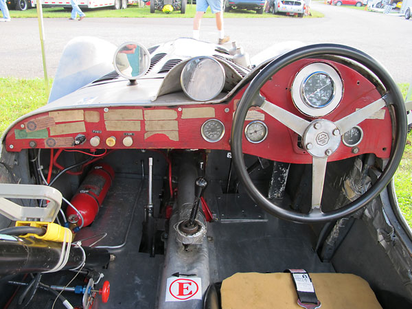 Lester MG KUR 4's wooden dashboard, with fourteen faded SCCA tech-inspection decals still attached.