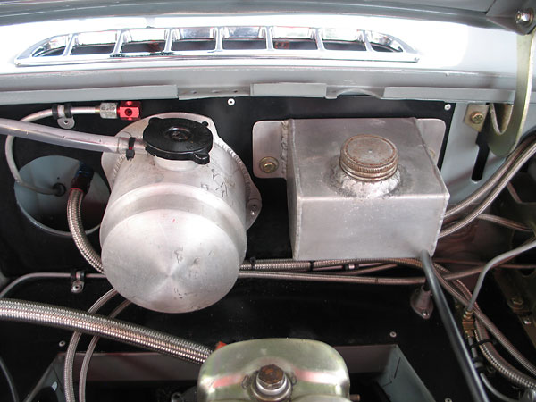 Coolant overflow tank (left) and brake system fluid reservoir (right).