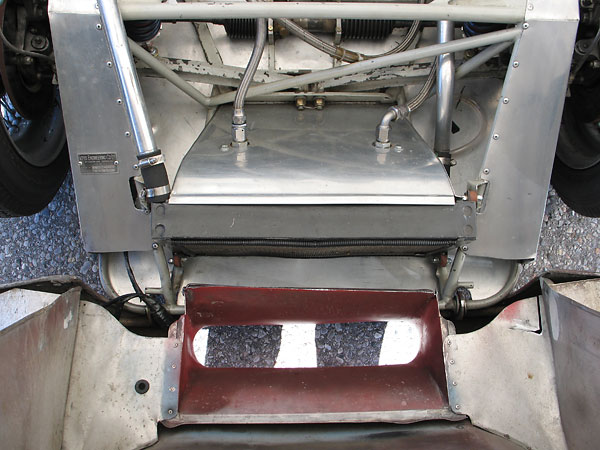 After passing through the radiator, airflow routes downward rather than through the engine compartment.