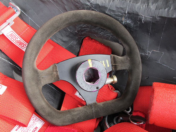 Alpha 255mm flat-bottom suede-covered steering wheel, mounted on a quick release hub.