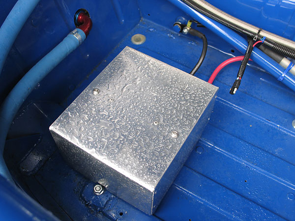 A lightweight AGM-type racing battery is mounted under this aluminum cover.