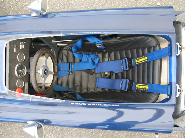 A comfortable looking seat, and a Schroth Racing six-point cam-lock safety harness.