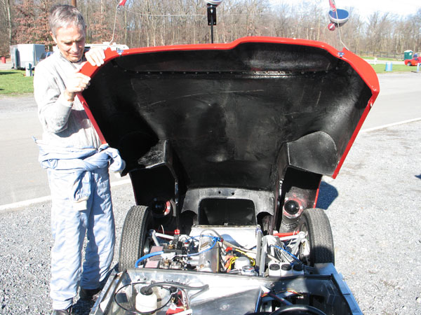 Tom holds open the bonnet of his Lola Sports Mark One race car.