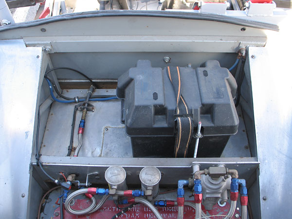 A large lead-acid battery is mounted in a marine battery box, behind the seat.